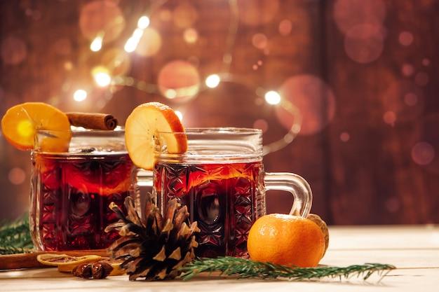 Heißer glühwein mit gewürzen im glasbecher auf einem hölzernen hintergrund. traditionelles weihnachtliches wärmendes getränk.