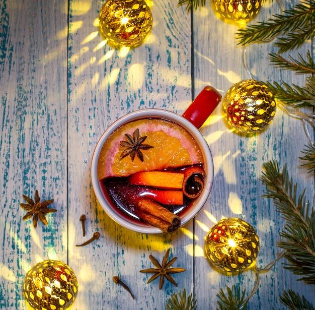 Heißer glühwein mit orange, anis und zimt auf dem hintergrund von weihnachtsbaumzweigen und girlande. erwärmendes weihnachtsgetränk.