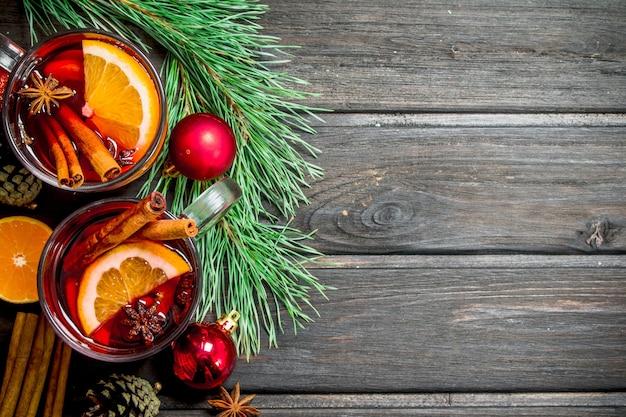 Heißer glühwein zu weihnachten mit gewürzen und aromatischen kräutern. auf einem hölzernen hintergrund.