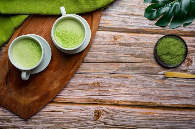 Heißer grüner tee in einem glas mit sahne und grünem tee, dekoriert mit grünem teepulver.