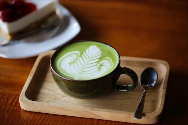 Heißer grüner tee matcha latte in der schale auf tabelle.