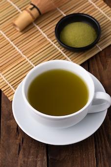 Heißer grüner tee mit pulver auf holz
