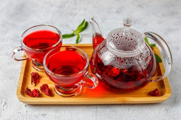 Heißer hibiskus-tee in einem glasbecher und einer glasteekanne.