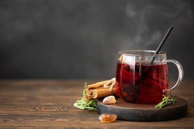 Heißer hibiskus-tee mit zimt und zucker auf einem holztisch