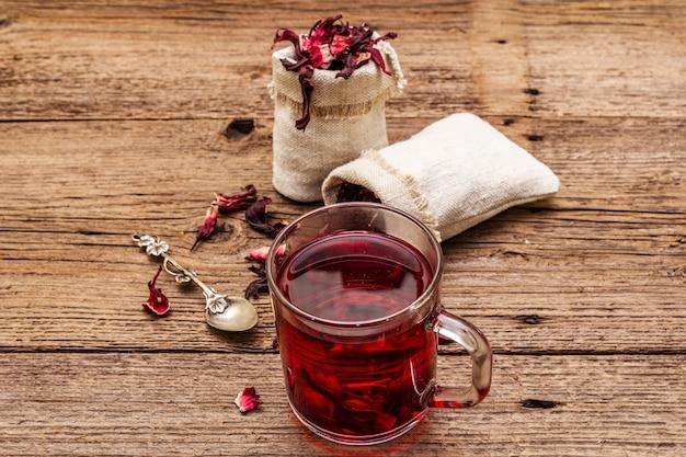 Heißer hibiskus-tee. trockene blütenblätter, leinensäcke. gesundes essen und self-care-konzept.