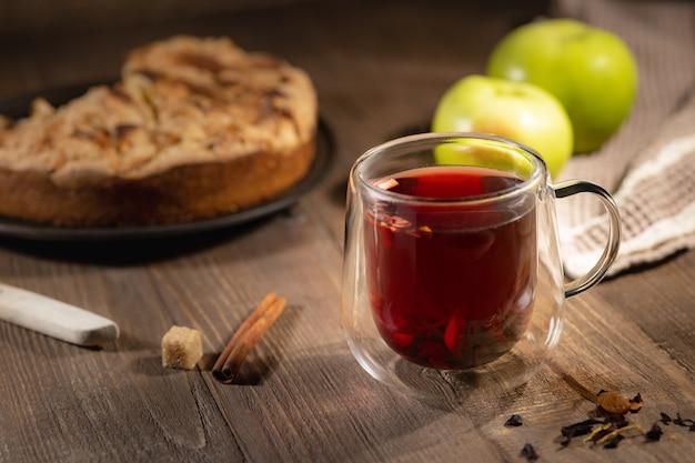 Heißer hibiskustee in doppelglastasse und selbst gebackener apfelkuchen, herbstliches frühstücksstillleben, selektiver fokus