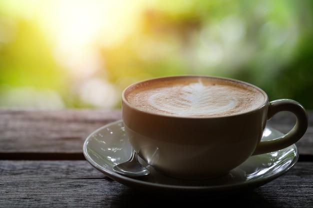 Heißer kaffee auf einem holztisch auf grünem hintergrund