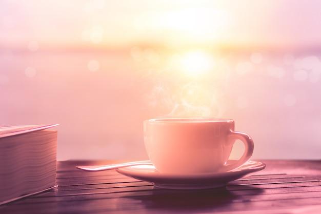 Heißer kaffee auf holztisch bei sonnenaufgang