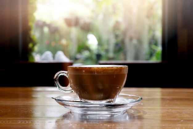 Heißer kaffee auf holztisch mit schöner aussicht des morgens über fenster