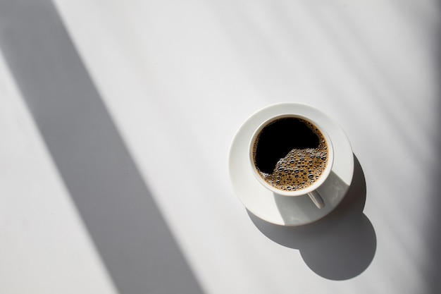 Heißer kaffee auf weißem tischhintergrund. platz für text. draufsicht
