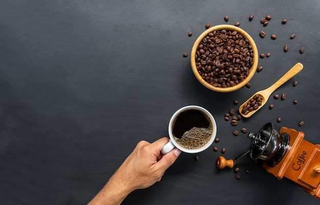 Heißer kaffee, bohne und handmühle auf schwarzem tischhintergrund. platz für text. draufsicht
