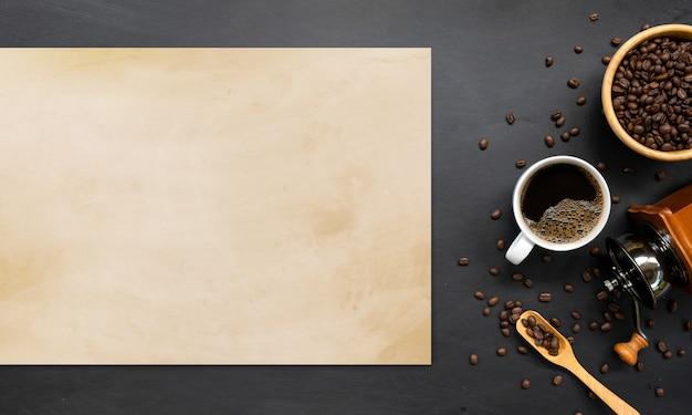 Heißer kaffee, bohne und handmühle auf weißem tischhintergrund. platz für text. draufsicht