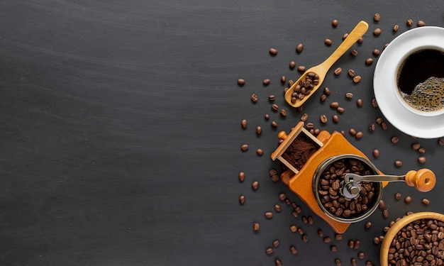 Heißer kaffee, bohnen und handmühle auf zementboden