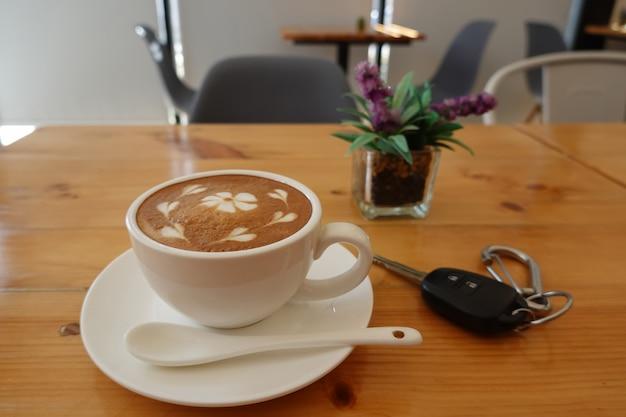 Heißer kaffee, cappuccino in einer weißen kaffeetasse auf einem kiefernholztisch und daneben liegt ein autoschlüssel