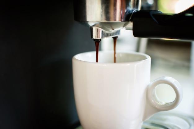 Heißer kaffee, der von der kaffeemaschine in die kaffeetasse fällt.