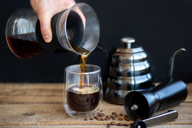 Heißer kaffee fließt in ein glas. kaffee durch einen trichter kochen. eine tasse frischen heißen filter. eine mühle mit einer teekanne und kaffeekörnern. duftendes heißes getränk. selbstgebrauter kaffee. kaffeepause