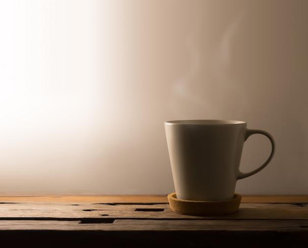 Heißer kaffee für den frühen morgen mit warmem licht auf dem tisch.