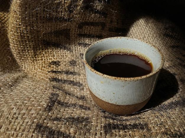 Heißer kaffee im traditionellen keramikbecher auf weinlese-kaffeebohnen-sack
