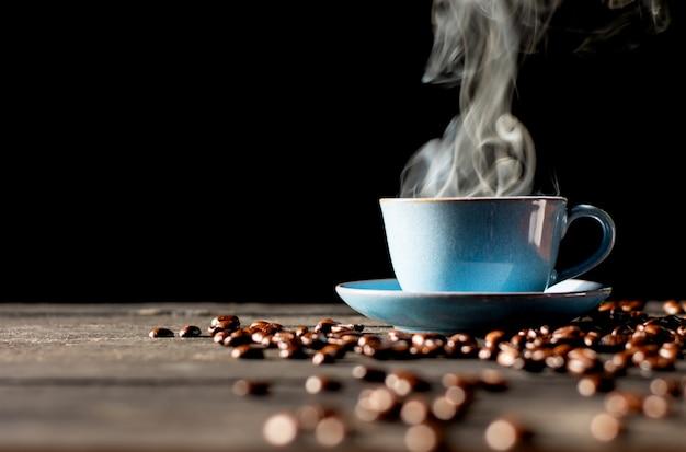 Heißer kaffee in blauer tasse und geröstete kaffeebohnen auf einem schwarzen holztisch.