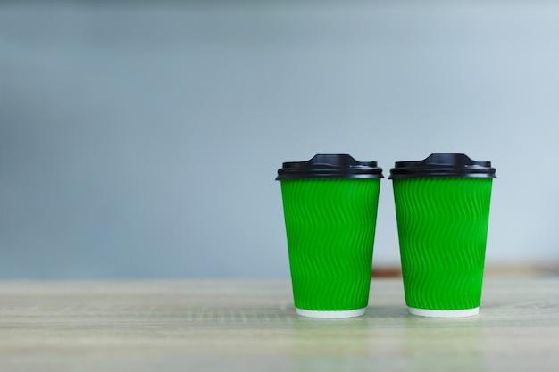 Heißer kaffee in der grünen mitnehmerpapierschale. kaffee zum mitnehmen im café-shop