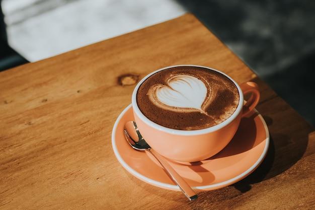 Heißer kaffee in der schale auf hölzerner tabellenweichzeichnung, getonter retro- effekt.
