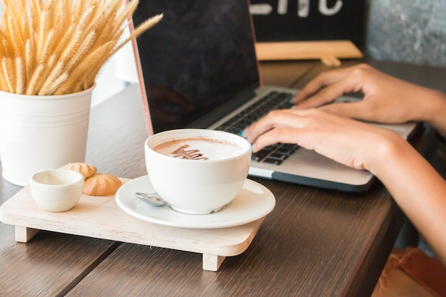 Heißer kaffee in der weißen schale mit den frauenhänden