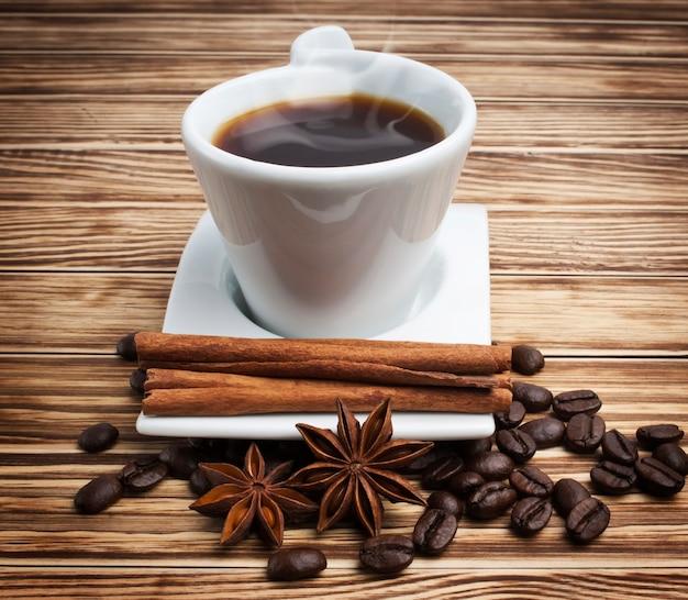 Heißer kaffee in der weißen tasse auf hölzernem hintergrund