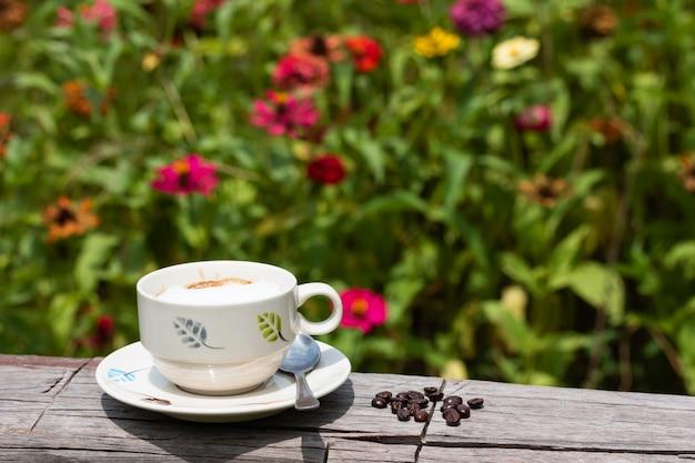 Heißer kaffee in einem glas auf dem bauholz im blumengarten