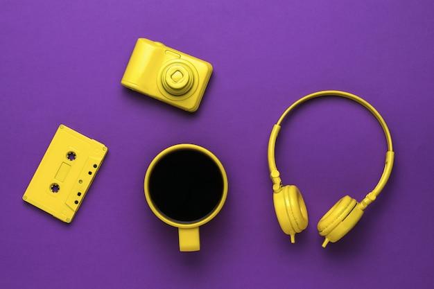 Heißer kaffee in einer gelben tasse, kopfhörer, eine kassette und eine kamera auf violettem hintergrund. farben-trend.