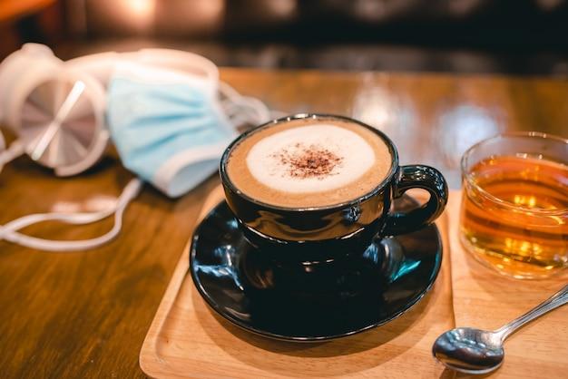 Heißer kaffee in einer schwarzen tasse und 1 tasse tee, der zusammen im café während des corona-virus oder covid-19 serviert wird