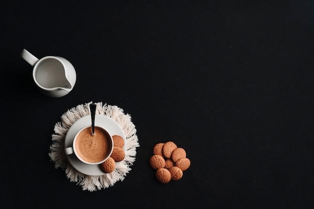Heißer kaffee in einer tasse mit einigen keksen auf einem teller und einem dunklen hintergrund. speicherplatz kopieren. draufsicht.