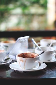 Heißer kaffee in einer tasse wird auf dem tisch mit soft-fokus und über licht im hintergrund getrunken