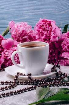 Heißer kaffee in einer weißen schale auf einer tabelle mit pfingstrosen der rosa farbe auf einem blauen hölzernen