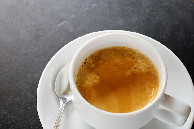 Heißer kaffee in einer weißen tasse im dunklen steintisch