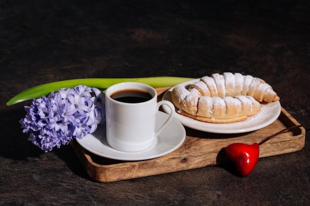 Heißer kaffee in weißer tasse croissantpulver und blumen blaue hyazinthe auf holztablett