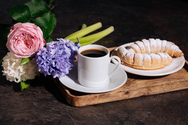Heißer kaffee in weißer tasse croissantpulver und blumen blaue hyazinthe rosa rose auf holztablett