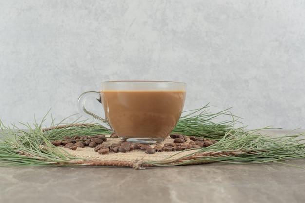 Heißer kaffee, kieferngras und kaffeebohnen auf marmoroberfläche.