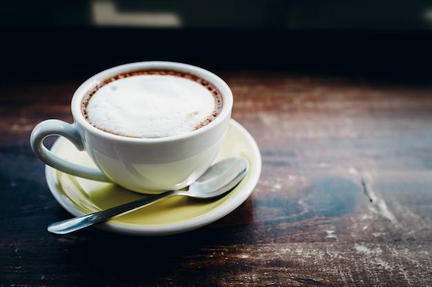 Heißer kaffee latte-cappuccinospiralenschaum auf holztisch im kaffeestubecafé mit weinlesefarbton-filterhintergrund.