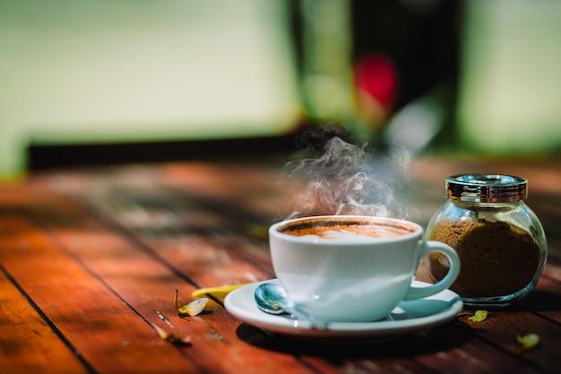 Heißer kaffee latte-cappuccinospiralenschaum auf holztisch in der kaffeestube