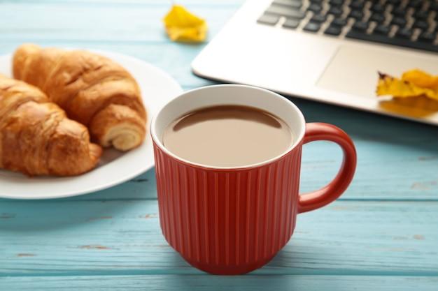 Heißer kaffee mit croissant und herbstlaub auf blau - saisonales entspannungskonzept. ansicht von oben