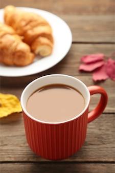 Heißer kaffee mit croissant und herbstlaub auf grau - saisonales entspannungskonzept. vertikales foto