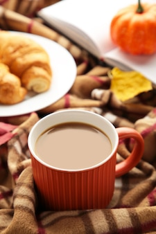 Heißer kaffee mit croissant und herbstlaub auf plaid - saisonales entspannungskonzept. vertikales foto