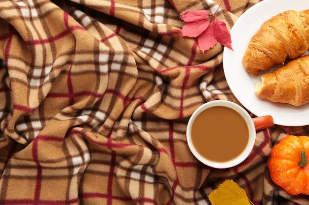Heißer kaffee mit croissant und herbstlaub auf plaid - saisonales entspannungskonzept