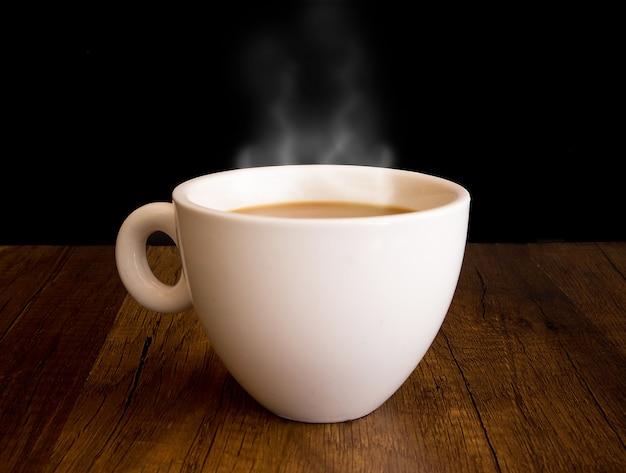 Heißer kaffee mit dampf aus einer schale heraus, auf holztisch und schwarzem hintergrund