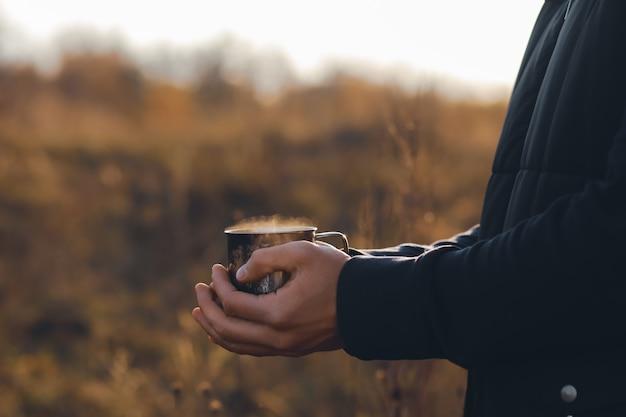 Heißer kaffee mit dampf in den händen eines mädchensherbstkomposition mit einer tasse kakaoheißer tee in