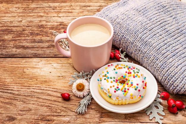 Heißer kaffee mit einem donut. herbstgetränk für gute laune mit plaid, frischen hagebutten, blättern und blüten.