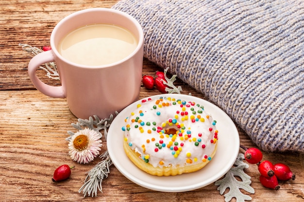 Heißer kaffee mit einem donut und einer dekoration