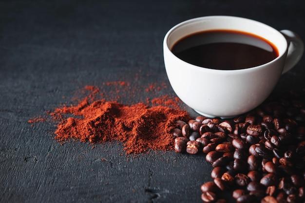 Heißer kaffee mit kaffeepulver und kaffeebohnen auf einem schwarzen hintergrund