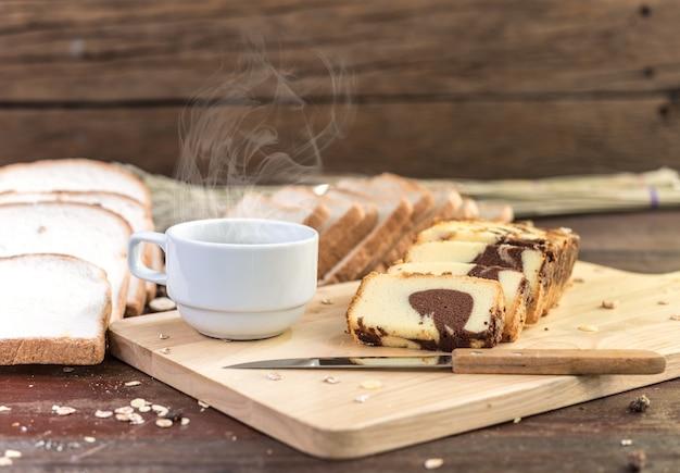 Heißer kaffee mit kuchen und brot auf holztisch