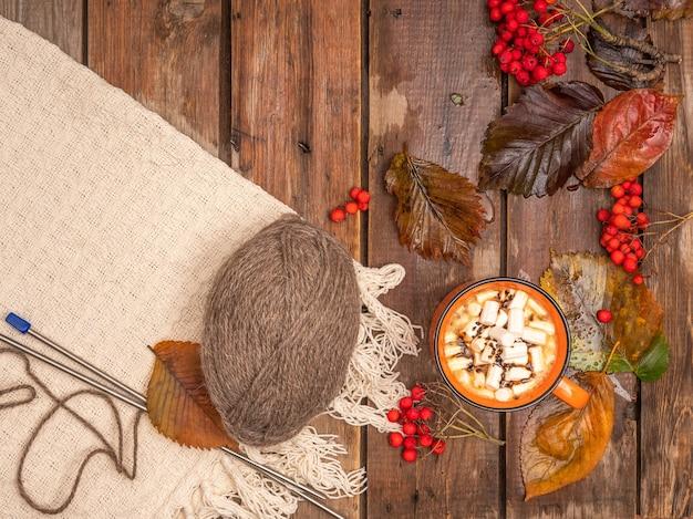 Heißer kaffee mit marshmallow serviert auf einem gemütlichen herbsttisch mit bunten blättern und einer decke